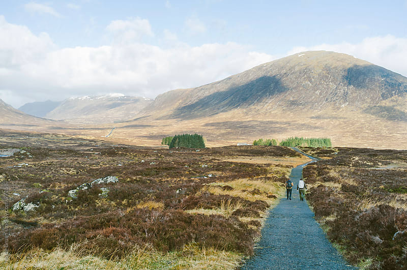 Two men walking or hiking in the Scottish Highlands by Ivo de Bruijn for Stocksy United