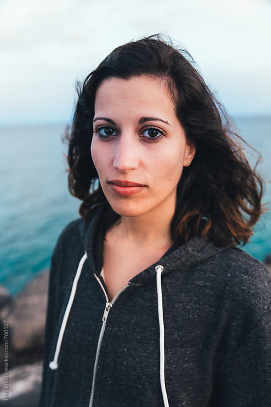 Portrait of a young woman on a pier looking at camera and wearing a grey sweatshirt by Inuk Studio for Stocksy United