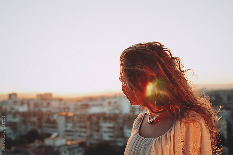 Portrait of a young woman on top of building at sunset by paff for Stocksy United