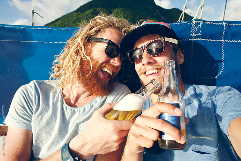 Two happy friends laughing and enjoying a beverage on a sailboat  by Denni Van Huis for Stocksy United