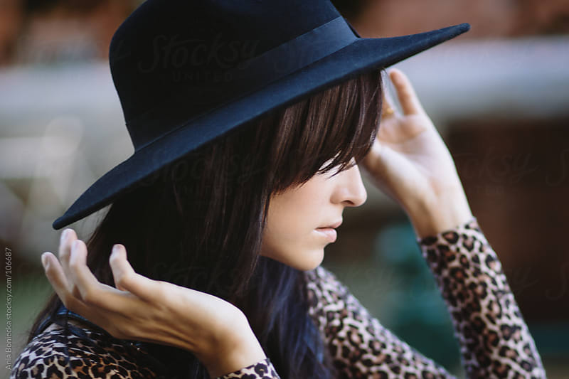 A profile portrait of a woman holding onto a wide brimmed black hat by Ania Boniecka for Stocksy United