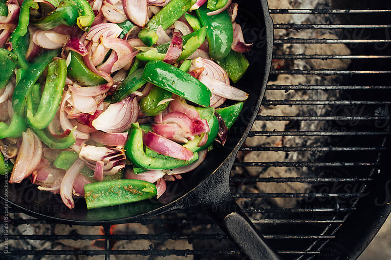 Peppers and onions for fajitas in a cast iron skillet by Gabriel (Gabi) Bucataru for Stocksy United