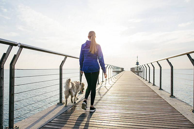 Back view of a woman walking with her dog on a bridge at morning. by BONNINSTUDIO for Stocksy United