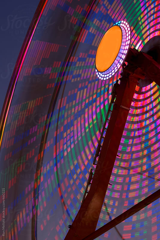 time exposure nighttime ferris wheel state fair amusement park color bands patterns by Ron Mellott for Stocksy United