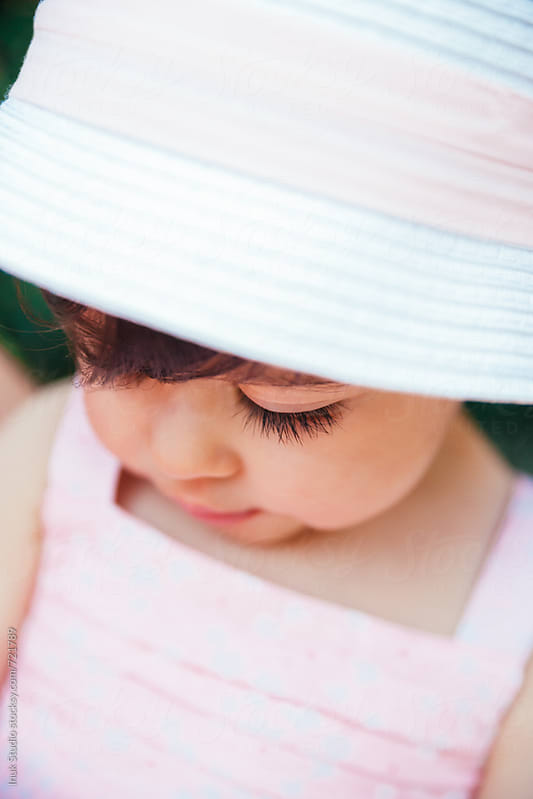 Baby girl portrait wearing a hat and pink dress by Inuk Studio for Stocksy United