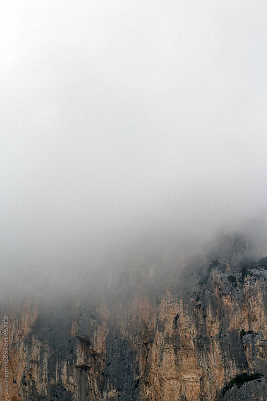 Cliff covered by clouds by Luca Pierro for Stocksy United