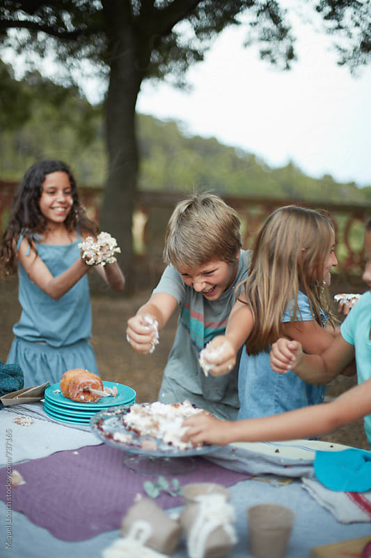End of a birthday party with children and cake war by Miquel Llonch for Stocksy United