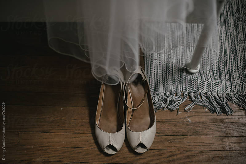 Vintage bridal wedding shoes on wood floor with veil by Daring Wanderer for Stocksy United