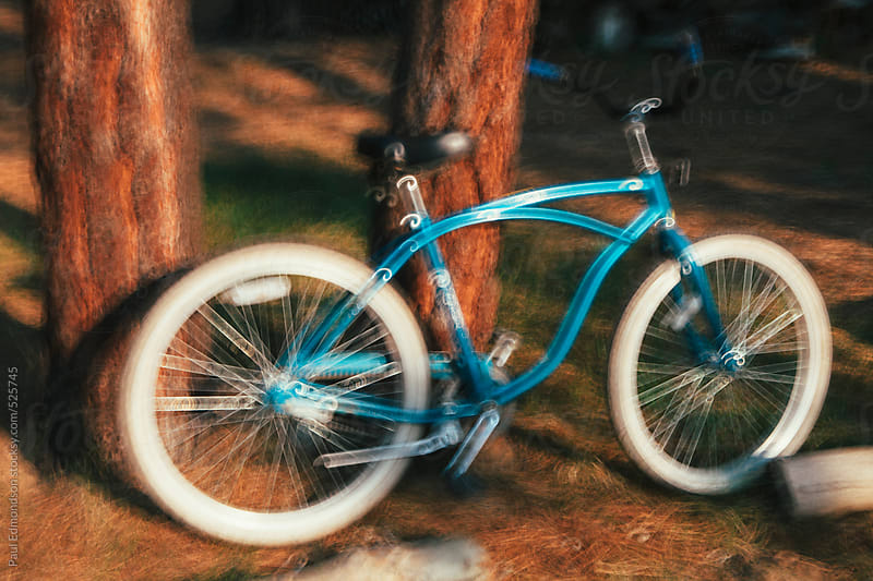Blurred focus of old cruiser bike leaning agains pine tree by Paul Edmondson for Stocksy United