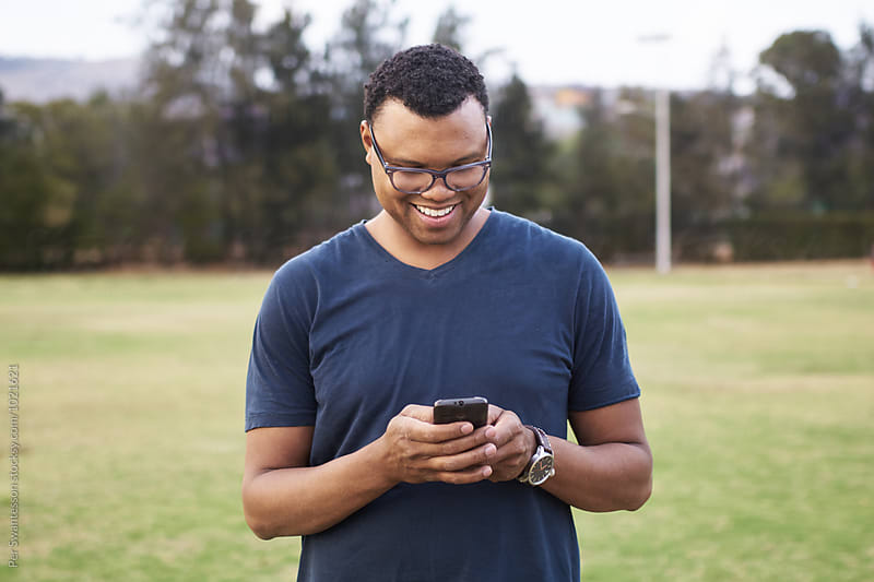 Happy black man using a cell phone in a park by Per Swantesson for Stocksy United