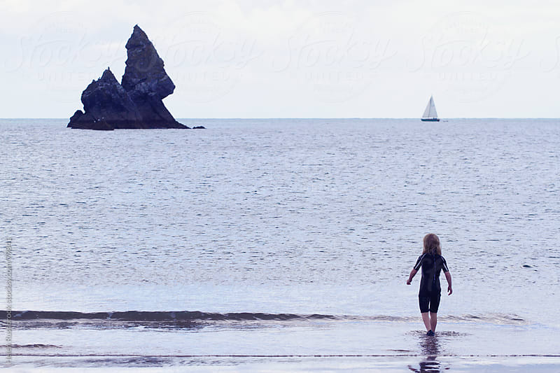 A little girl in a wetsuit walking into the sea. by Helen Rushbrook for Stocksy United