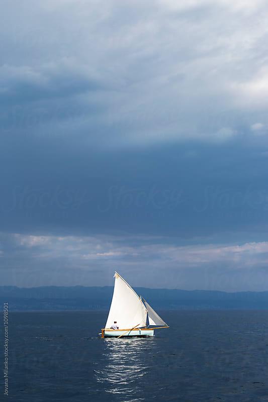 Traditional wooden sailboat  sailing the dark blue sea