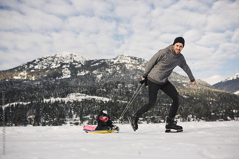 Young dad having fun skating and pulling kids on frozen lake ice by Rob and Julia Campbell for Stocksy United