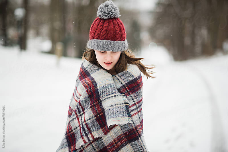 young woman in the snow wrapped in blanket by Léa Jones for Stocksy United