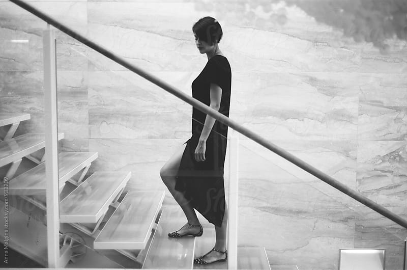 A black and white film portrait of a young beautiful woman on stairs by Anna Malgina for Stocksy United