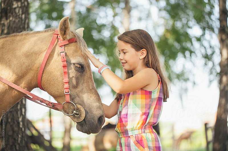 Smiling Girl Petting a Horse by Lumina for Stocksy United