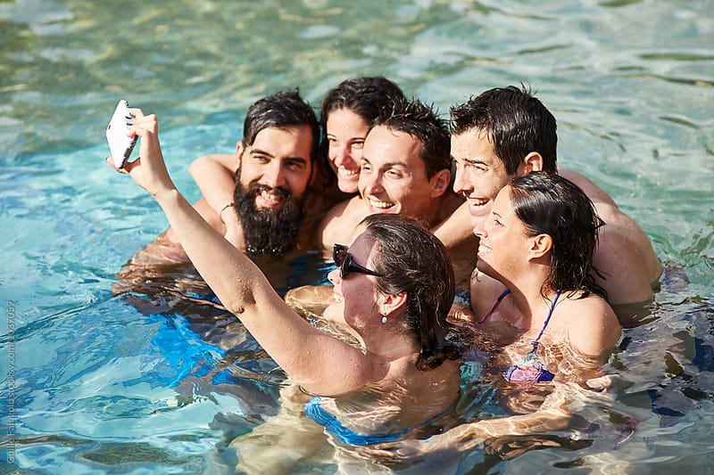 Happy friends making selfie in pool in sunlight by Guille Faingold for Stocksy United