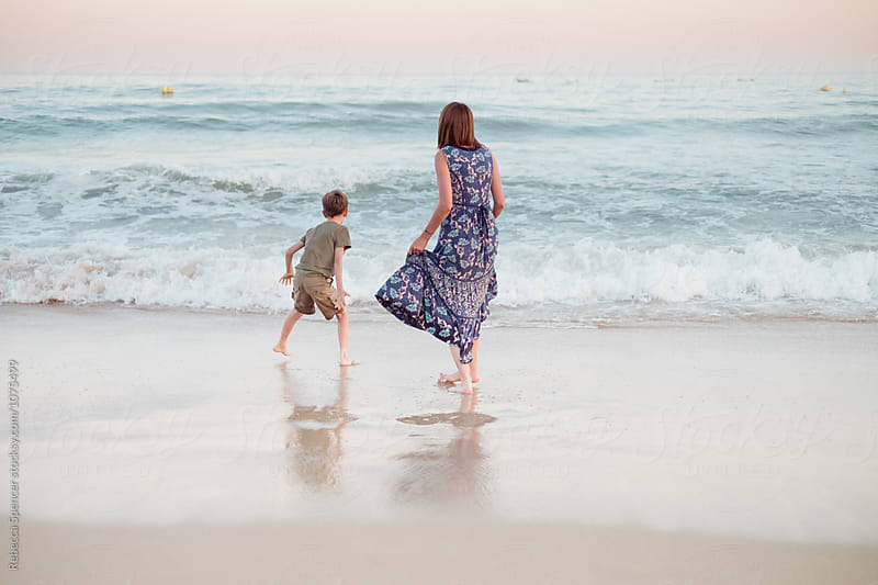 Boy and Mum get ready to jump over sea waves by Rebecca Spencer for Stocksy United