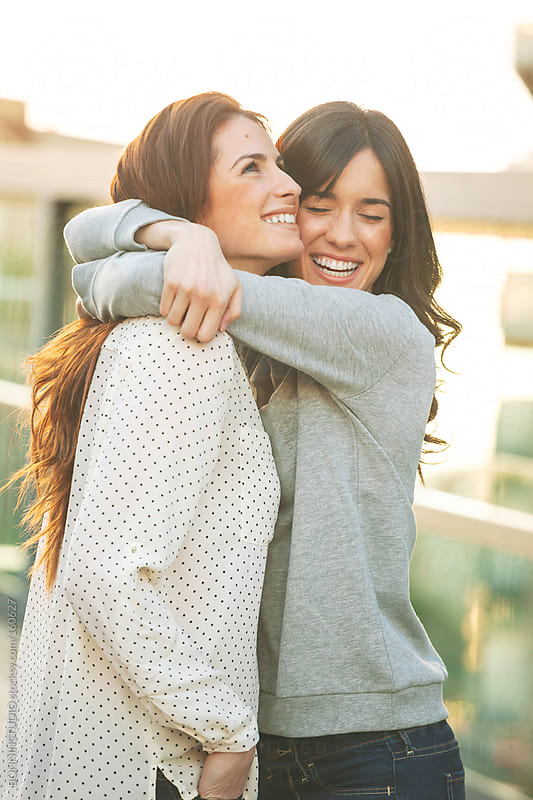 Happy young girlfriends hugging together on the city. by BONNINSTUDIO for Stocksy United
