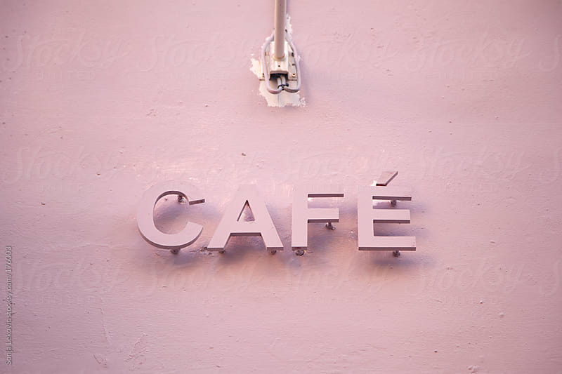 french cafe sign on a pink wall by Sonja Lekovic for Stocksy United