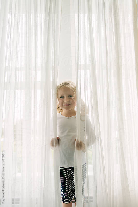 Portrait of Young Girl Hiding in the Curtains by Raymond Forbes LLC for Stocksy United