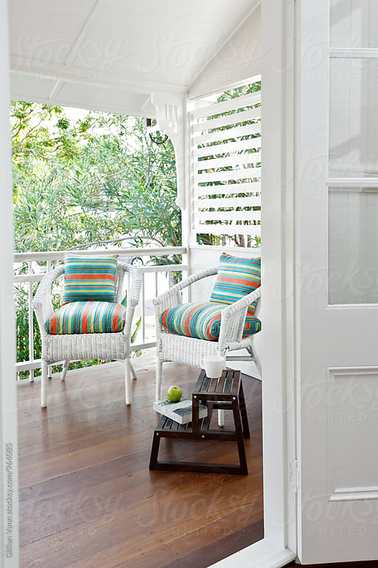 small porch or verandah with wicker chairs, a book and a cup of tea by Gillian Vann for Stocksy United