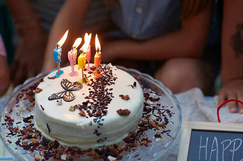 Close up of a birthday cake with candles by Miquel Llonch for Stocksy United