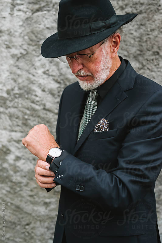 Classy elegant senior man watching the time by Simone Becchetti for Stocksy United