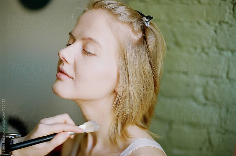 Applying  makeup for the young woman by Lyuba Burakova for Stocksy United