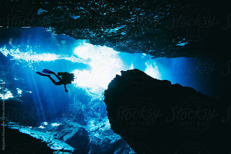 Silhouette of scuba diver exploring an underwater cave in a cenote in Yucatán Peninsula, Mexico by Alejandro Moreno de Carlos for Stocksy United