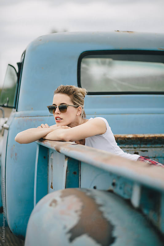 Blond girl  wearing sunglasses in the back of a pickup truck int by Ania Boniecka for Stocksy United