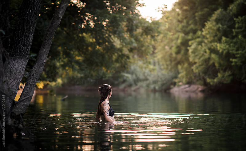 Young Woman Swimming In Creek by Jack Sorokin for Stocksy United
