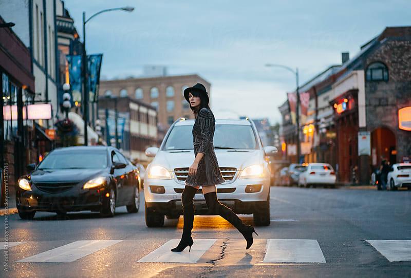 A stylish woman walking on a crosswalk at dusk by Ania Boniecka for Stocksy United