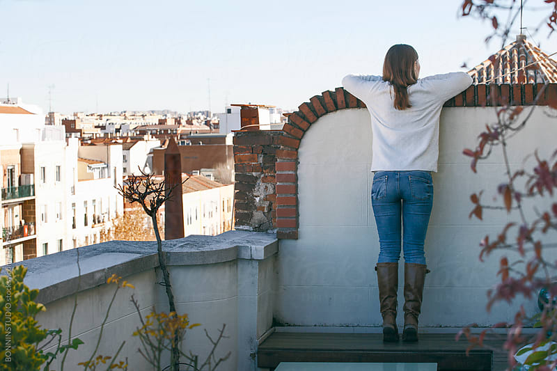 Young woman looking a cityscape from the terrace. Back view. by BONNINSTUDIO for Stocksy United