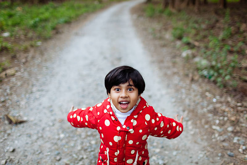 Happy child on a gravel road in the forest by Saptak Ganguly for Stocksy United