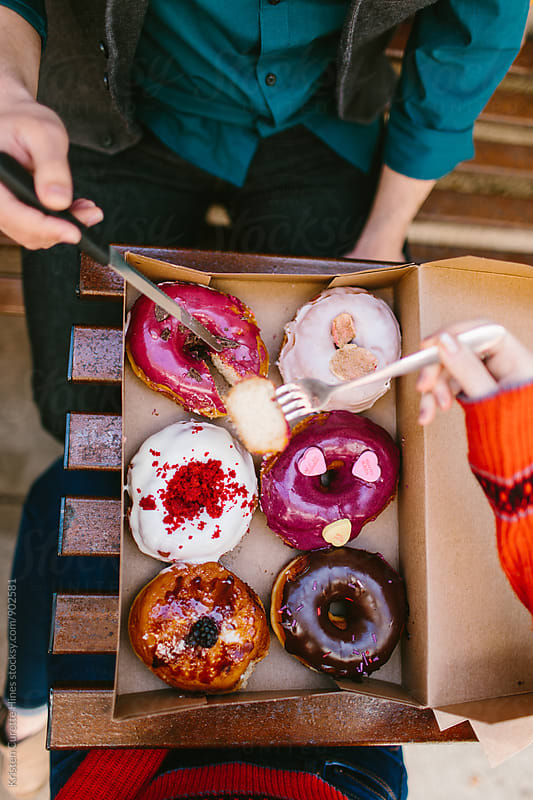Birds eye view of two people eating a box of donuts  by Kristen Curette Hines for Stocksy United