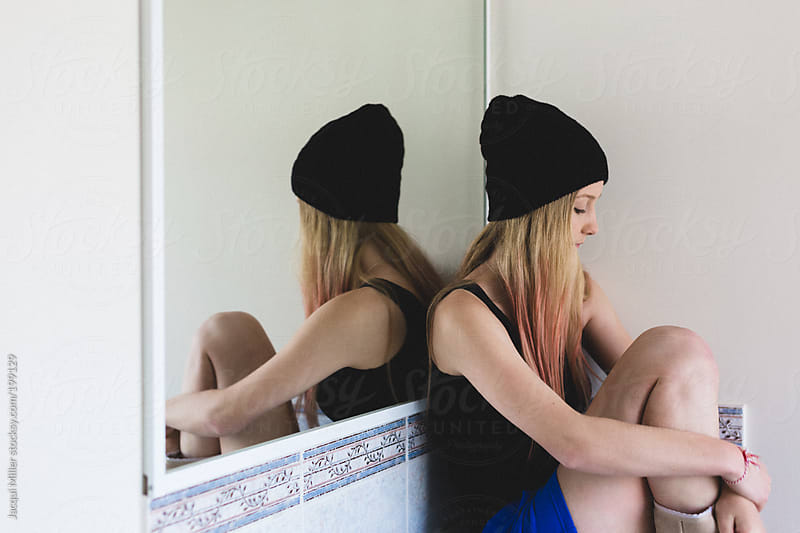 Contemplative teen girl, with pink dyed hair, sits in a bathroom with her back against a mirror by Jacqui Miller for Stocksy United