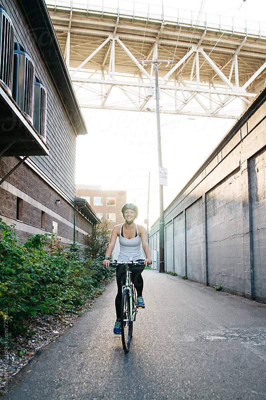 young female riding bicycle in alley way  by Jesse Morrow for Stocksy United