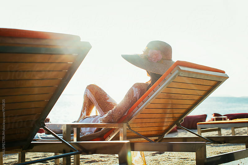 Pretty Young Caucasian Woman Wearing Large Straw Hat Relaxing on Beach Sunbed by VISUALSPECTRUM for Stocksy United