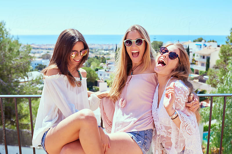 Three girls having fun against of summer cityscape and sea by Guille Faingold for Stocksy United