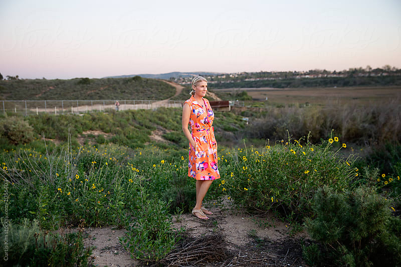 Blonde woman standing in meadow during sunset by Curtis Kim for Stocksy United