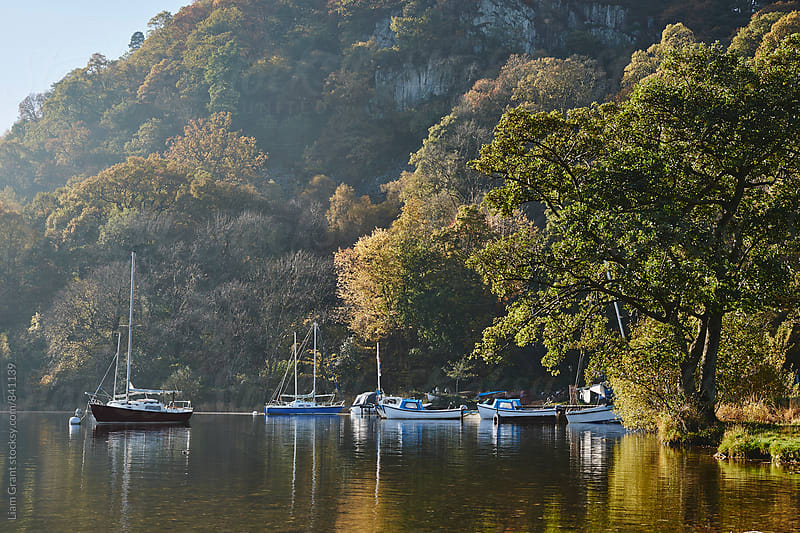 Boats and autumnal colour. Ullswater, Cumbria, UK. by Liam Grant for Stocksy United