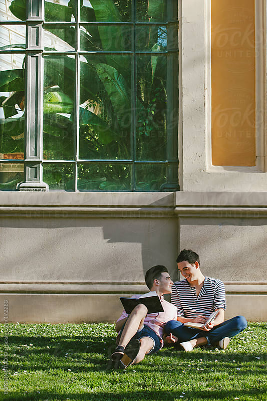 Smiling gay couple reading a book sitting on the grass of a park in front a greenhouse. by BONNINSTUDIO for Stocksy United