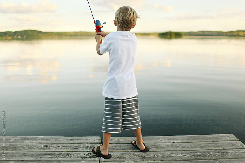 young child fishing from a pier by Kelly Knox for Stocksy United