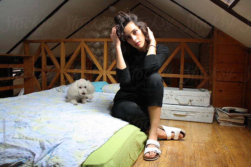 Young woman and white poodle sitting on the bed by VeaVea for Stocksy United