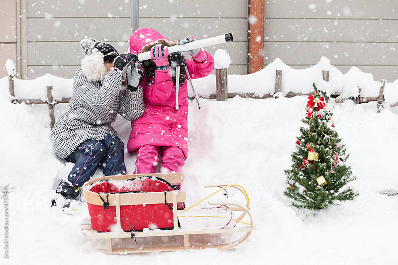 two sister playing telescope on snow by jira Saki for Stocksy United