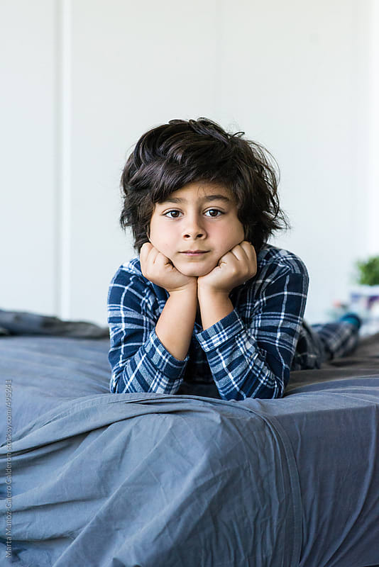 Black and white portrait of a spanish boy in his pajamas on bed  by Marta Muñoz-Calero Calderon for Stocksy United