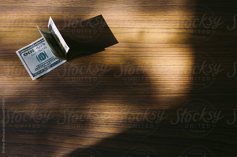 Hundred dollar bills on a wooden table. by Shikhar Bhattarai for Stocksy United