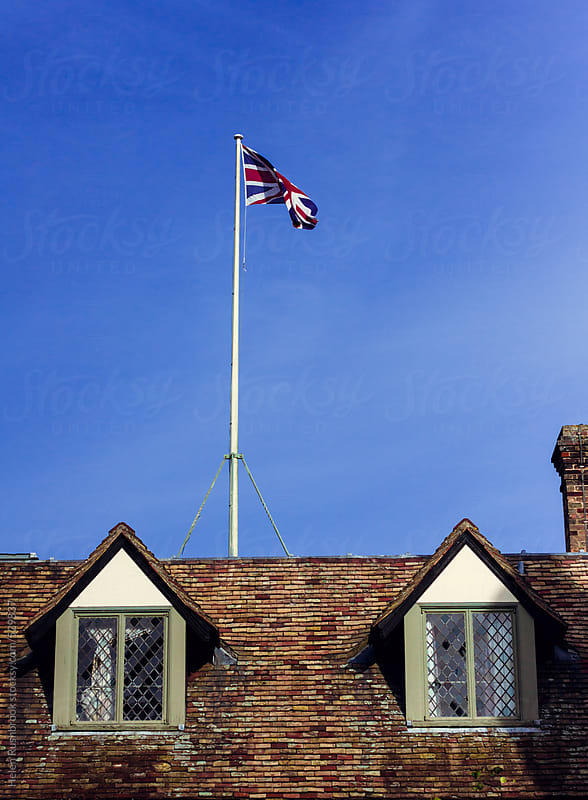 Union Jack flag flying over an old building by Helen Rushbrook for Stocksy United