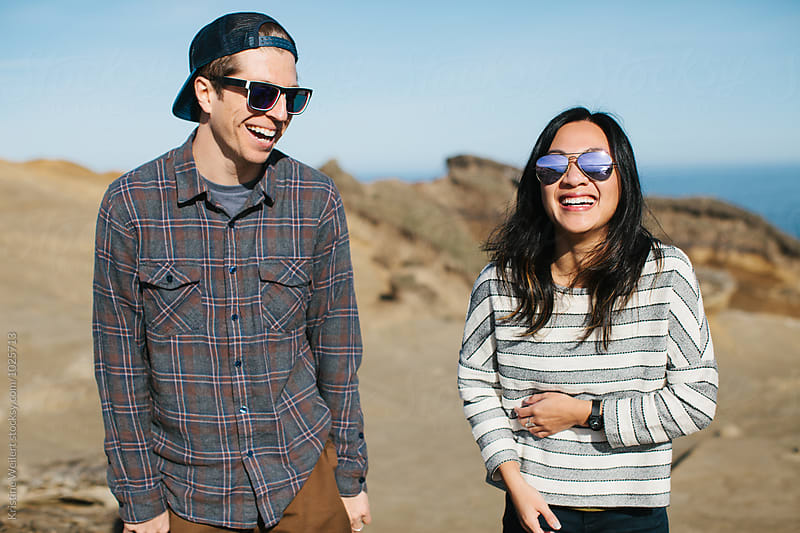 Two hip friends smiling and laughing with eachother by Kristine Weilert for Stocksy United